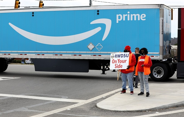 People hold a banner at the Amazon facility as members of a congressional delegation arrive to show their support for workers who will vote on whether to unionize, in Bessemer, Alabama, US March 5, 2021. Photo: Reuters