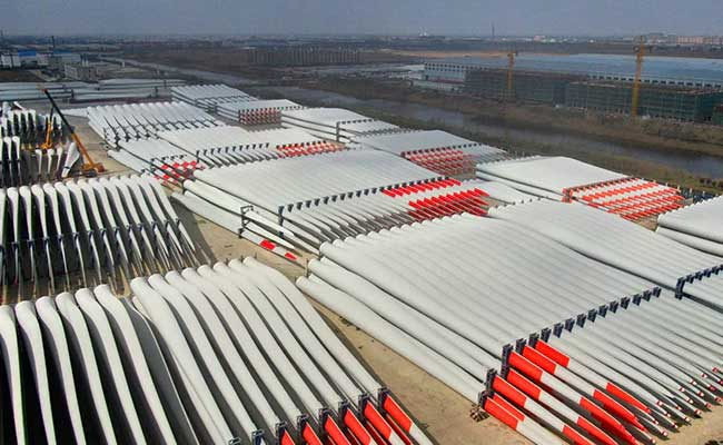 Wind turbine blades wait for export at a factory in Nantong in eastern China on March 2, 2021. (AFP)