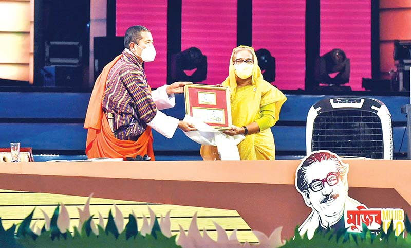 Bhutanese Prime Minister Dr Lotay Tshering presenting  a commemorative stamp to Prime Minister Sheikh Hasina at National Parade Ground in the capital on Wednesday.PHOTO: PID