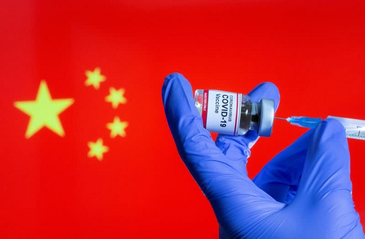 """A woman holds a small bottle labeled with a """"Coronavirus COVID-19 Vaccine"""" sticker and a medical syringe in front of displayed China flag in this illustration. File photo: Reuters"""