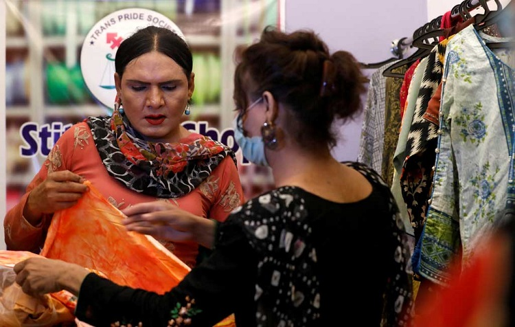 Jiya, 35, a transgender woman and tailor, talks with a customer at her shop in Karachi, Pakistan April 5, 2021. Photo: Reuters/Akhtar Soomro