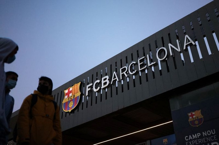 FILE PHOTO: Youths walk past Barcelona soccer club logo outside of Camp Nou stadium in Barcelona, Spain January 15, 2021. REUTERS/Nacho Doce