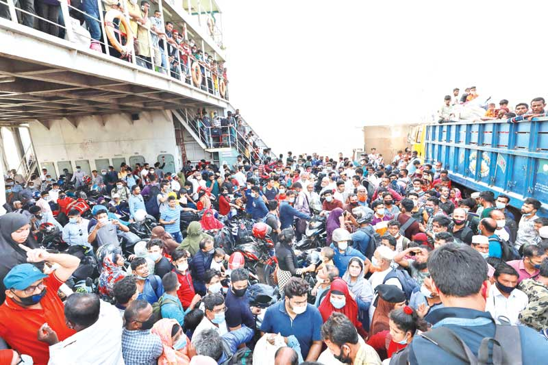 Thousands of people cram Shimulia ferry terminal to go to their village homes flouting Covid health safety guidelines  on Tuesday.PHOTO: OBSERVER