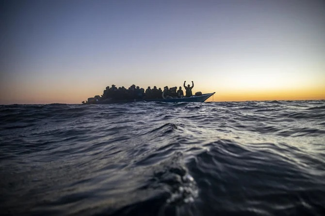 Migrants and refugees wait for assistance aboard an overcrowded wooden boat in the Mediterranean Sea, off the coast of Libya, Feb. 12, 2021. (AP Photo)