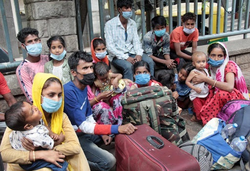 Indian migrant workers and their families are seen outside the bus transport booking center during coronavirus pandemic, in Bangalore, India, April, 1
