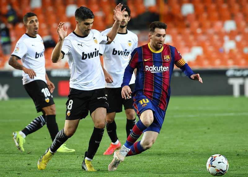 Valencia's Spanish midfielder Carlos Soler (2L) challenges Barcelona's Argentinian forward Lionel Messi during the Spanish League football  match between Valencia and Barcelona at the Mestalla stadium in Valencia on May 2, 2021.photo: AFP