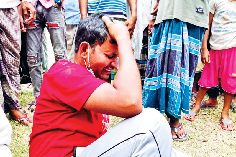 District and naval police, divers of Fire Service and Civil Defence, ferry ghat authorities along with locals are conducting rescue operation after at least 26 people were killed as a speedboat overturned after hitting a sand-laden bulkhead anchored in Padma in Madaripur's Shibchar upazila on Monday. Inset, a relative of a victim breaks down in tears. PHOTO: OBSERVER
