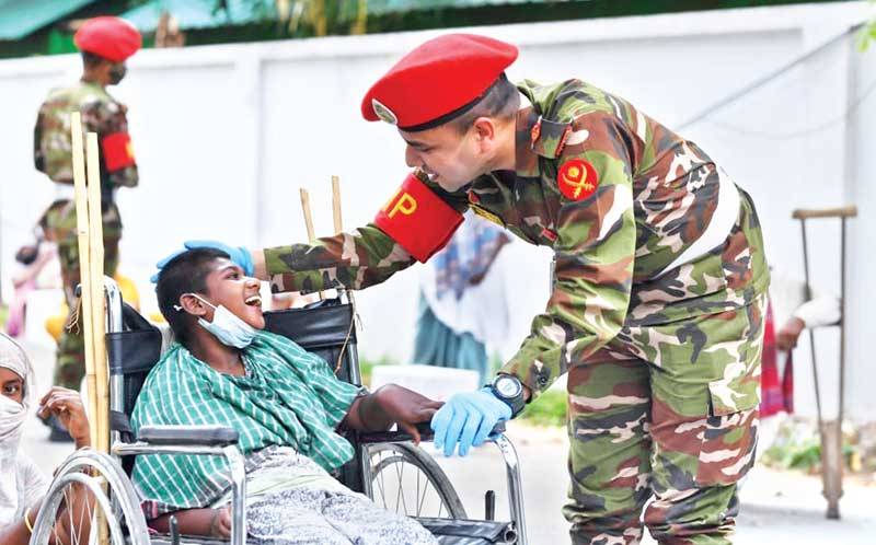 The Military Police unit on Tuesday distributing relief materials among the jobless, distressed and underprivileged people to survive the pandemic in Dhaka Cantonment's nearby areas of Banani, Cantonment Rail Gate and Bhasantek on Tuesday. 	photo : ISPR