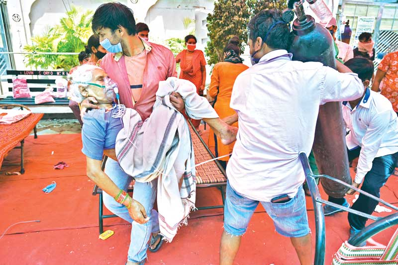 A family member carries a patient breathing with the help of oxygen being provided by a Gurdwara, a place of worship for Sikhs, under a tent installed along the roadside amid Covid-19 coronavirus pandemic in Ghaziabad on May 4.photo : AFP