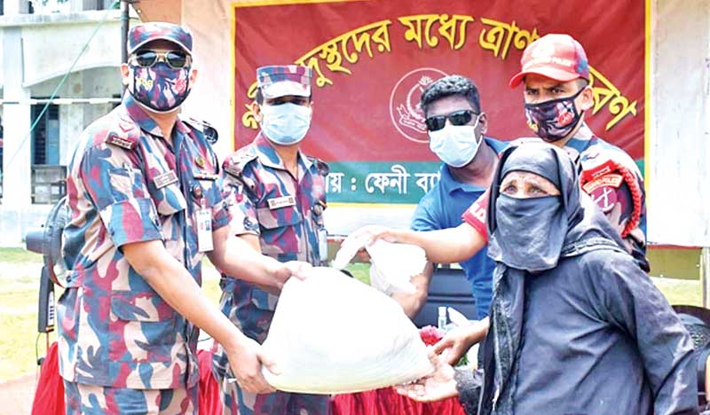 BGB and RAB personnel distributing food among poor in Feni