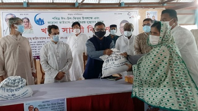 Health Minister Zahid Maleque distributes food items among coronvirus affected destitute families at Shuvra Centre in Garpara area under Manikganj Sadar upazila on Friday afternoon.