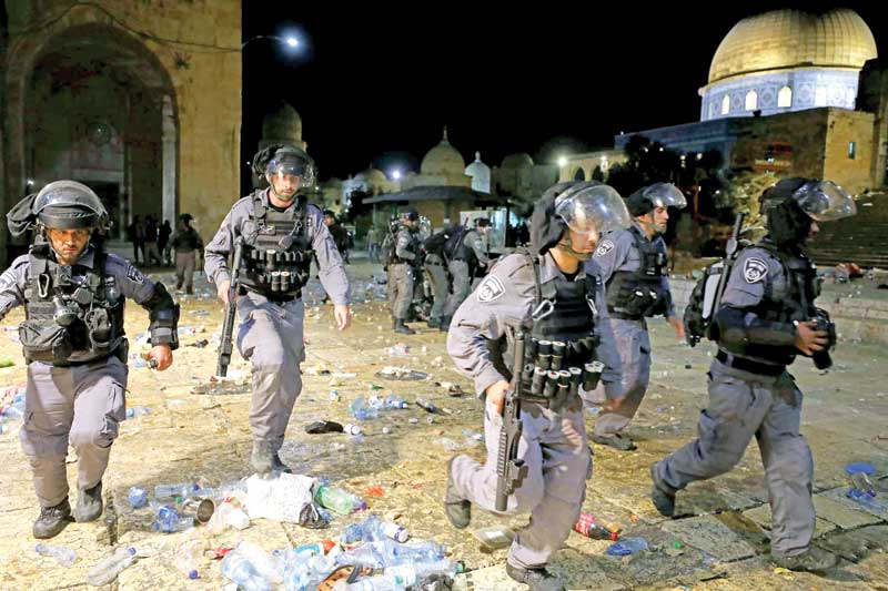 Israeli police run during clashes with Palestinians at the compound that houses