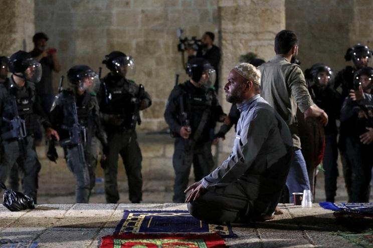 A Palestinian man prays as Israeli police gather at Al-Aqsa Mosque compound [Ammar Awad/Reuters]