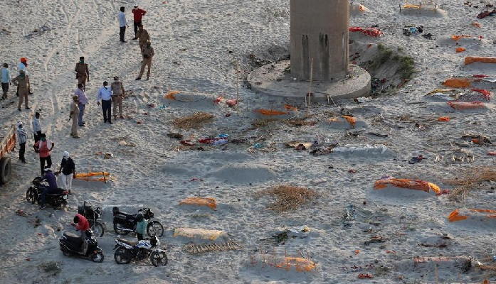 Policemen stand next to the bodies buried in shallow graves on the banks of Ganges river in Prayagraj, India, Saturday, May 15, 2021. (AP Photo)