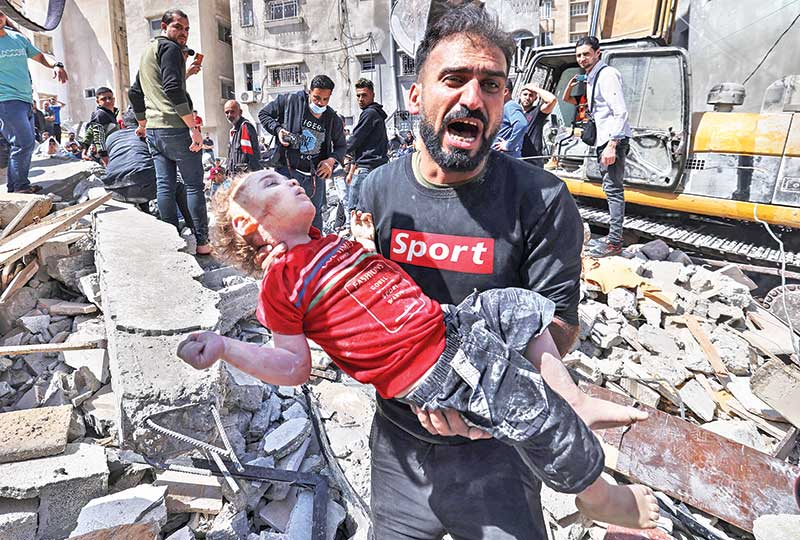 A Palestinian man recovers the body of a child from the rubble of a destroyed building in Gaza on May 16, following massive Israeli bombardment on the Hamas-controlled enclave. photo : AFP
