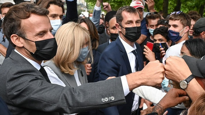 French President Emmanuel Macron (L) and his wife Brigitte Macron (C) interact with members of a crowd while visiting Valence on June 8, 2021 during a visit in the French southeastern department of Drôme, the second stage of a nationwide tour ahead of next year's presidential election. Photo: AFP