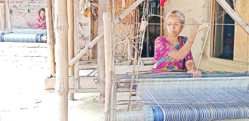 The photo shows Parul Begum waiving handloom cloth in Maria Village at Bagatipara. photo: observer