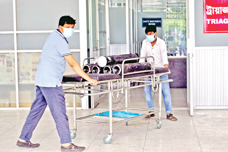 Oxygen cylinders are being brought in to Dhaka Medical College Hospital on Friday, apparently as preparation to cope with the situation amid the rise in Covid-19 infection in different areas of the country.   PHOTO: OBSERVER