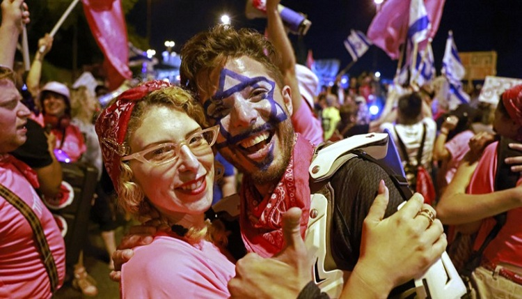 Israeli demonstrators celebrate the passing of a vote confirming a new coalition government during a rally in front of the Knesset during a parliamentary vote, in Jerusalem on Sunday. —AFP photo