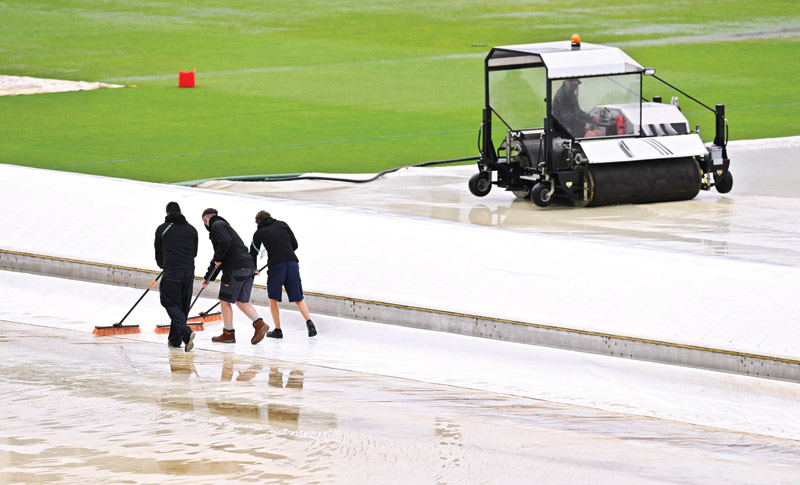 Ground staff sweep water from the covers as rain delays start of play on the first day of the ICC World Test Championship Final between New Zealand and India at the Ageas Bowl in Southampton, southwest England on June 18, 2021.photo: AFP