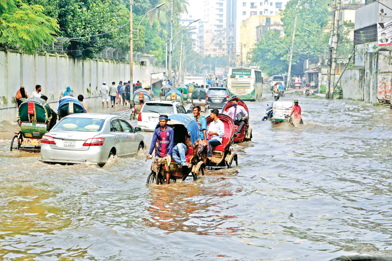 Vehicles struggle through a flooded road near Bangabhaban in the capital as moderate rain inundated several areas of the city on Monday.PHOTO: OBSERVER