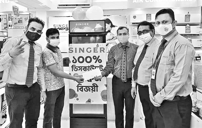 A customer receiving a refrigerator with 100% discount through scratch card at Banani, Dhaka, Singer Mega shop recently.