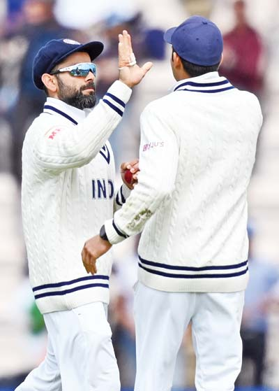 India's Virat Kohli (L) celebrates taking the wicket of New Zealand's captain Kane Williamson (unseen) for 49 runs on the fifth day of the ICC World Test Championship Final at the Ageas Bowl in Southampton, southwest England on June 22, 2021.photo: AFP