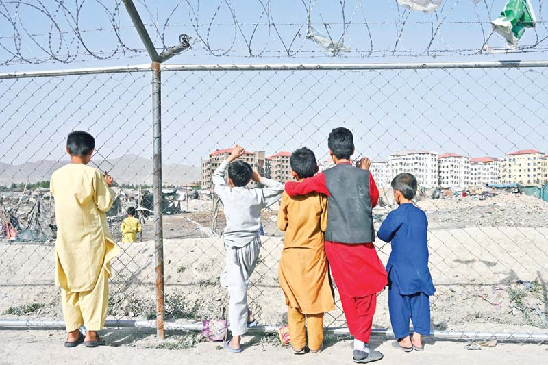 Children watch people at a camp for internally displaced people