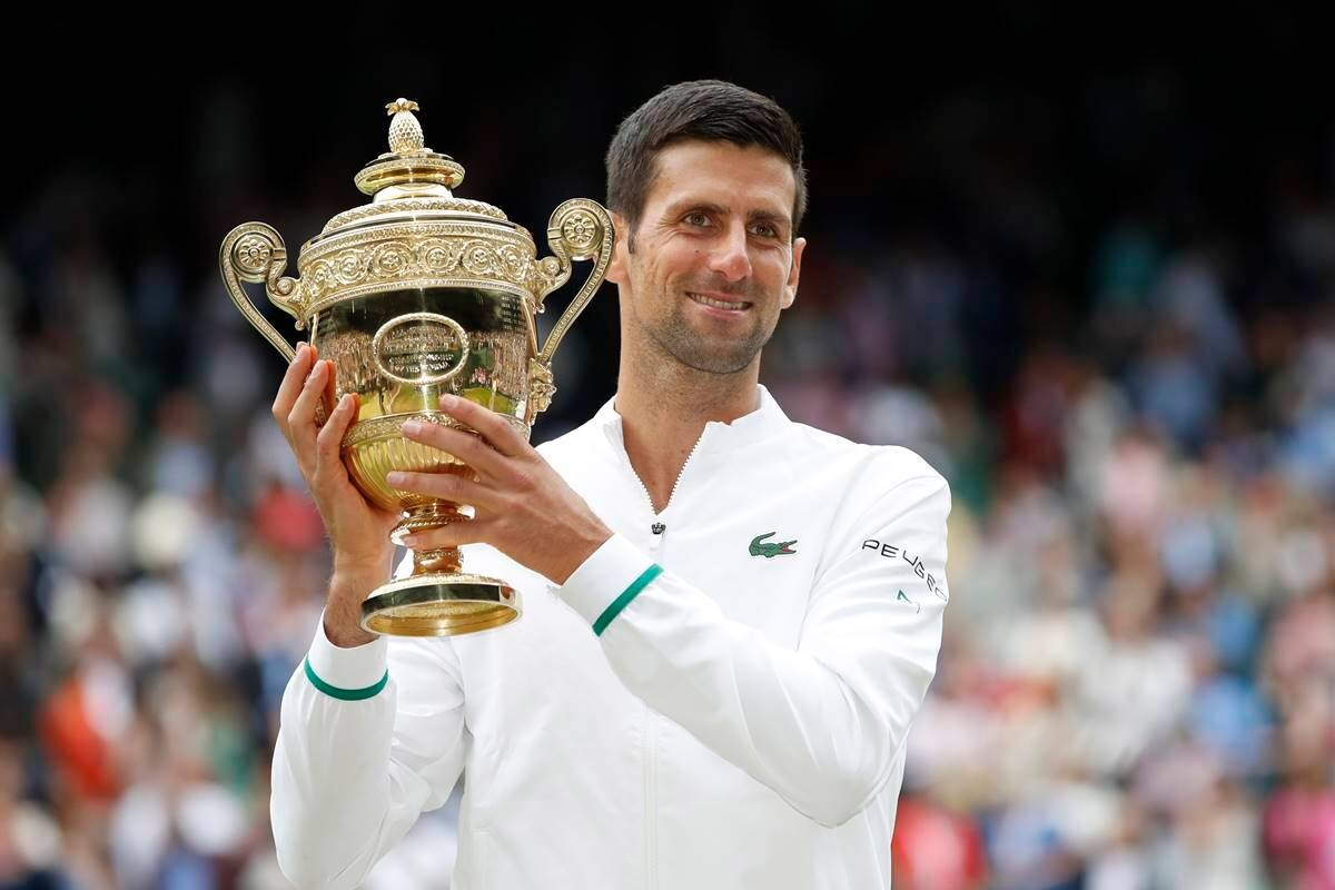 Serbia's Novak Djokovic celebrates with the trophy after winning his final match against Italy's Matteo Berrettini during Wimbledon 2021 at All England Lawn Tennis and Croquet Club, London, Britain. (Reuters image)