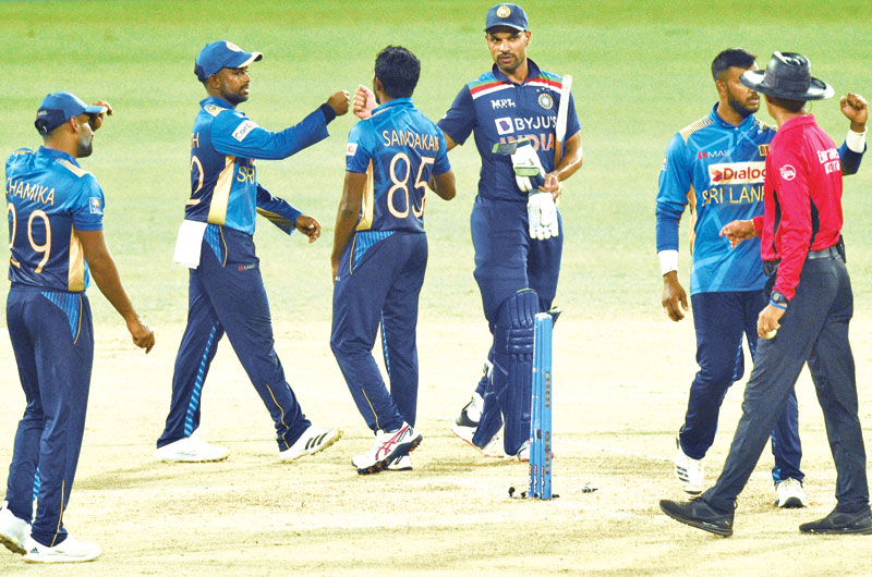 Indian cricket captain Shikhar Dhawan (3R) fist bumps with Sri Lankan fielders as he walks off the pitch after India defeated Sri Lanka by seven wickets in their first one day international (ODI) cricket match between Sri Lanka and India at The R.Premadasa Stadium in Colombo on July 18, 2021.photo: AFP