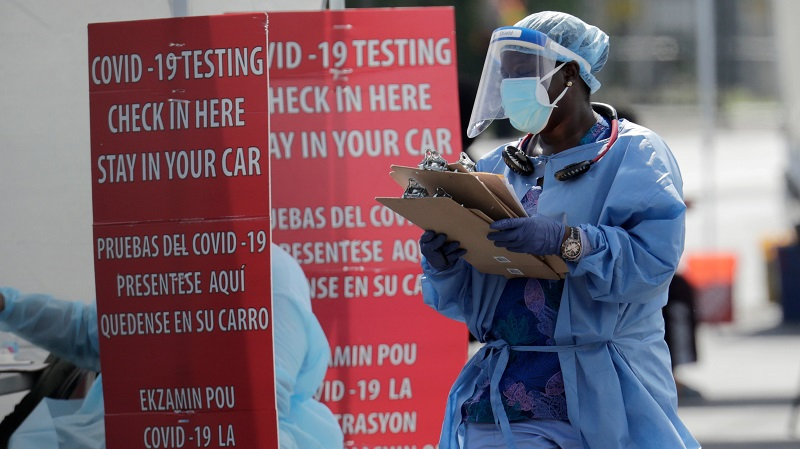 A healthcare worker carries a stack of clipboards at a COVID-19 testing site sponsored by Community Heath of South Florida, U.S., July 6, 2020.