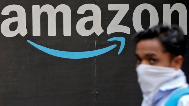 A man walks past an Amazon logo outside the company's collection point in Mumbai, India, March 19, 2021. REUTERS