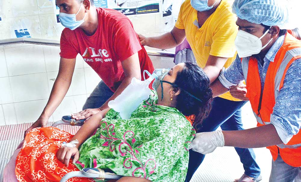 A Covid-19 infected woman under oxygen support is brought to Dhaka Medical College Hospital for treatment on Tuesday. PHOTO: OBSERVER