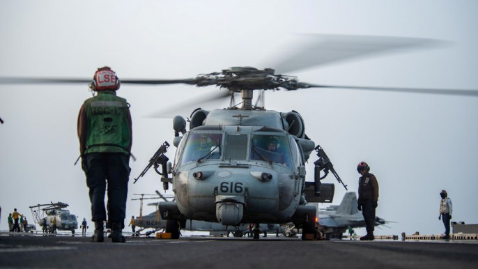 """Sailors prepare an MH-60S Sea Hawk helicopter, attached to the """"Golden Falcons"""" of Helicopter Sea Combat Squadron (HSC) 12, to launch on the flight deck of aircraft carrier USS Ronald Reagan (CVN 76), in response to a call for assistance from the Mercer Street, a Japanese-owned Liberian-flagged tanker managed by Israeli-owned Zodiac Maritime, in the Arabian Sea, in the Arabian Sea July 30, 2021. Picture taken July 30, 2021. U.S. Navy/Handout via REUTERS"""