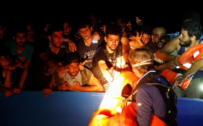 A RHIB (rigid hulled inflatable boat) crew member from the German NGO migrant rescue ship Sea-Watch 3 distributes life jackets to migrants. REUTERS