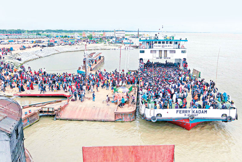 Dhaka-bound passengers get down from a crowded ferryboat at Shimulia terminal on Sunday as people from the southern districts, including a large number of export-oriented factory workers, start for the capital after temporary lifting of      restriction on plying of inter-district water transport during the ongoing lockdown starting from July 23. PHOTO: OBSERVER