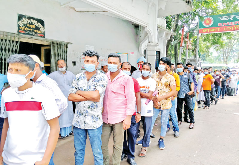 Expatriates willing to go abroad wait in a long queue for taking Covid-19 vaccine at Dhaka Medical College Hospital  on Monday.