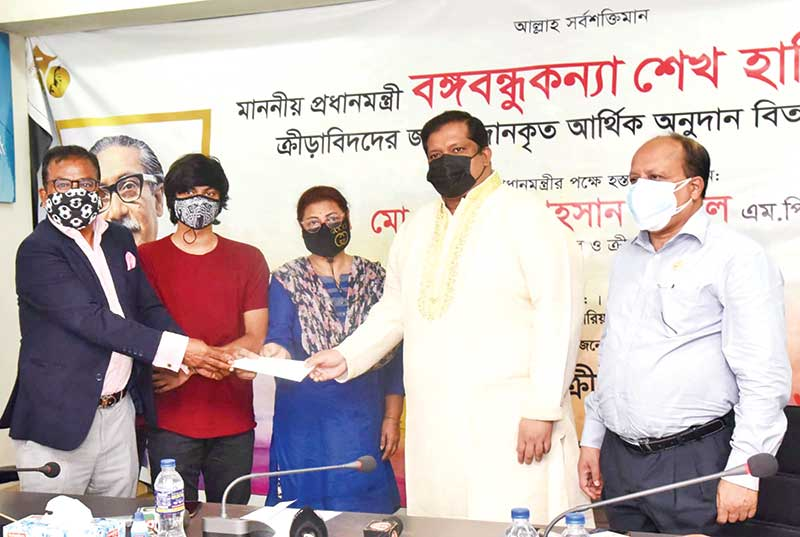 The State Minister for Youth and Sports Zahid Ahsan Russel, on behalf of Prime Minister Sheikh Hasina, handing over the documents of a gifted flat house and a check of Taka 2,500,000 to the family members of former star booter Badal Roy's wife Madhuri Roy on Wednesday.