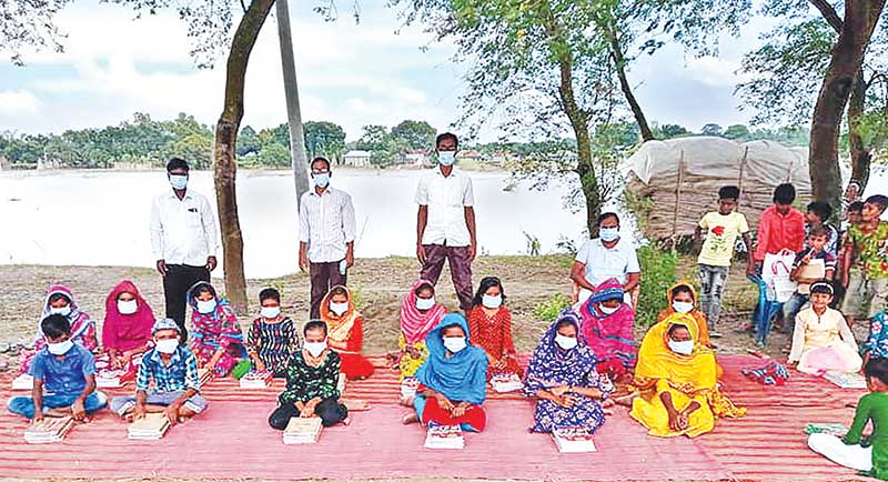 Students of Laxminagar Government Primary School in Bagha Upazila of Rajshahi attending classes under the open sky on Tuesday. photo: observer