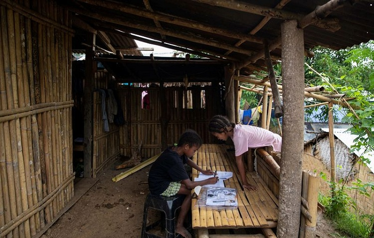 Seventh grade student Ryza Delos Santos, 10, works on her modules at home as her cousin observes, after a session at the makeshift rickshaw distance learning center for the Aeta community in Porac, Pampanga, Philippines, October 12, 2020. File photo: Reuters/Eloisa Lopez