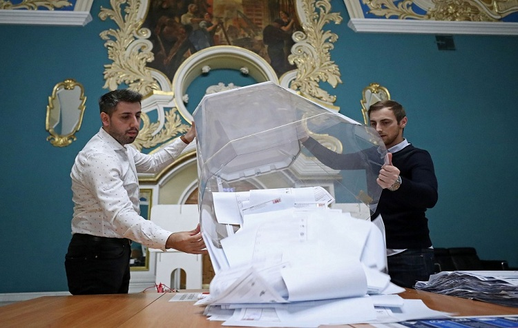 Members of a local election commission empty a ballot box after polls closed during a three-day long parliamentary election, at a polling station inside Kazansky railway terminal in Moscow, Russia September 19, 2021. Photo: Reuters