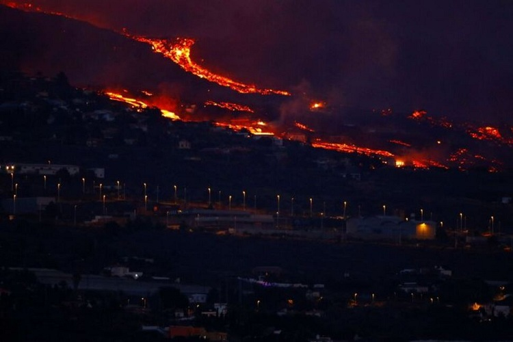 Lava flows behind houses following the eruption of a volcano in the Cumbre Vieja national park, in this picture taken from Tazacorte, on the Canary Island of La Palma, September 20, 2021. Photo: Reuters