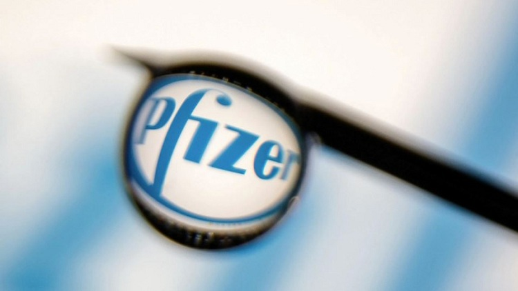 Pfizer logo is reflected in a drop on a syringe needle in this illustration photo taken March 16, 2021. Picture taken March 16, 2021. REUTERS