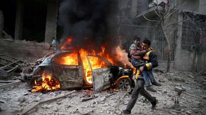 A Syrian Civil Defence member carries a wounded child in the besieged town of Hamoria, Eastern Ghouta [File: Reuters]