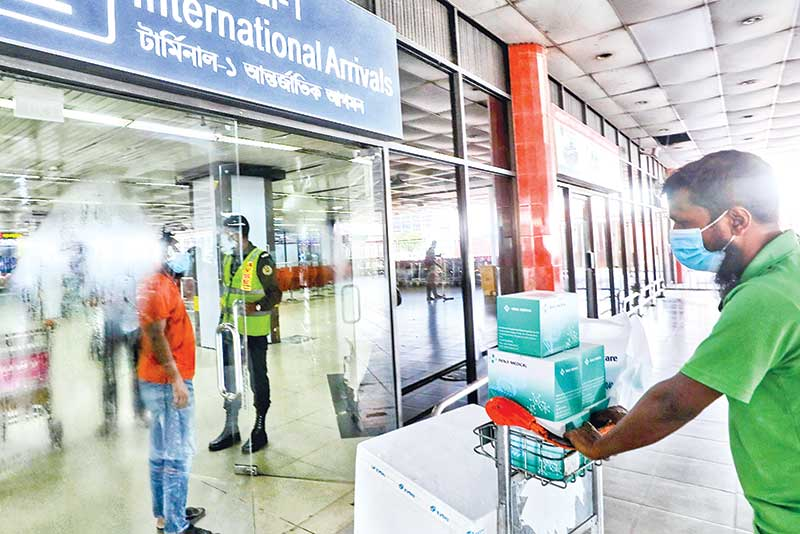 A worker with RT-PCR test equipment enters the terminal of Hazrat Shahjalal International Airport in the capital on Saturday as the authorities have set up a lab for rapid Covid-19 test for the passengers.  PHOTO: OBSERVER