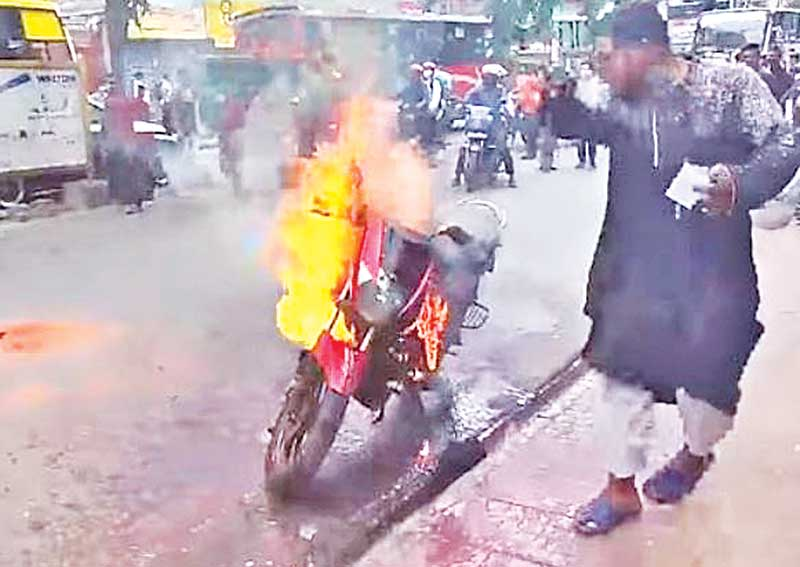 angry Protest against police harassment: Ridesharing biker Shawkat Alam Sohel standing next to his motorcycle after setting it on fire in the capital's Badda Link Road in Gulshan area on Monday morning against police action. PHOTO: OBSERVER