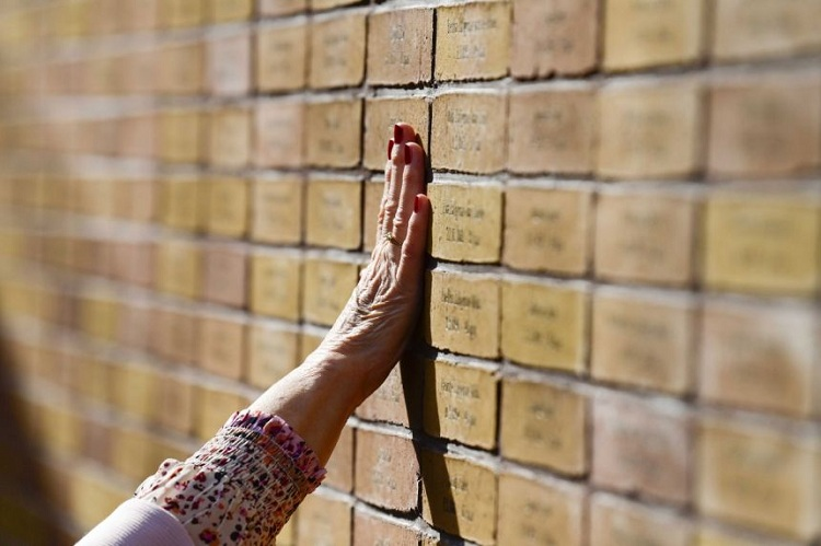 A woman places her hand at the Holocaust Memorial of Names in Amsterdam. Time is running out for prosecutors seeking to bring former members of the SS to justice as the war-time generation disappears. Photo: EPA-EFE