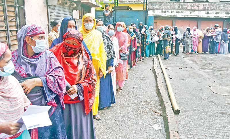 People coming for inoculation against Covid-19 wait in a long queue at Narinda Fakir Chan Community Centre in the capital during the countrywide mass vaccination programme marking Prime Minister Sheikh Hasina's 75th birthday on Tuesday. (Inset) A woman receives vaccine at a centre at Moghbazar in the city. PHOTO: OBSERVER
