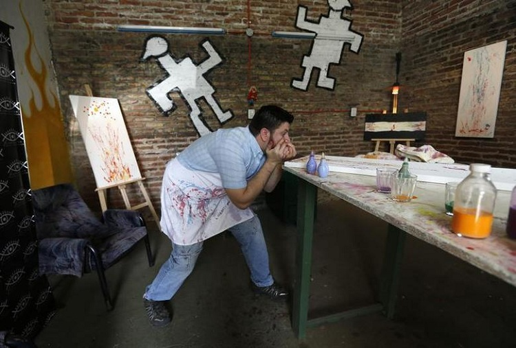 Artist Leandro Granato squirts paint from his eye onto a canvas at his studio in the Alejandro Korn town in greater Buenos Aires October 10, 2013. REUTERS/Enrique Marcarian